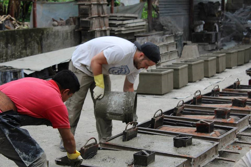 An OSU student helps a factory worker to pour concrete into plancha molds.